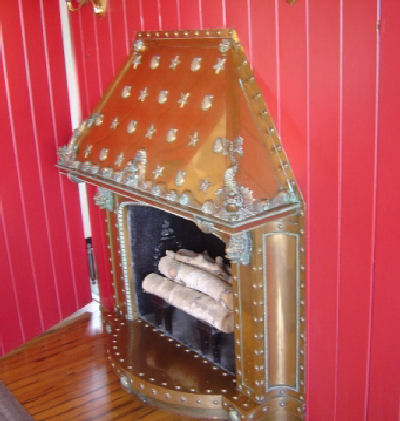 A brass fireplace adorned with shells, starfish, and sea serpents.